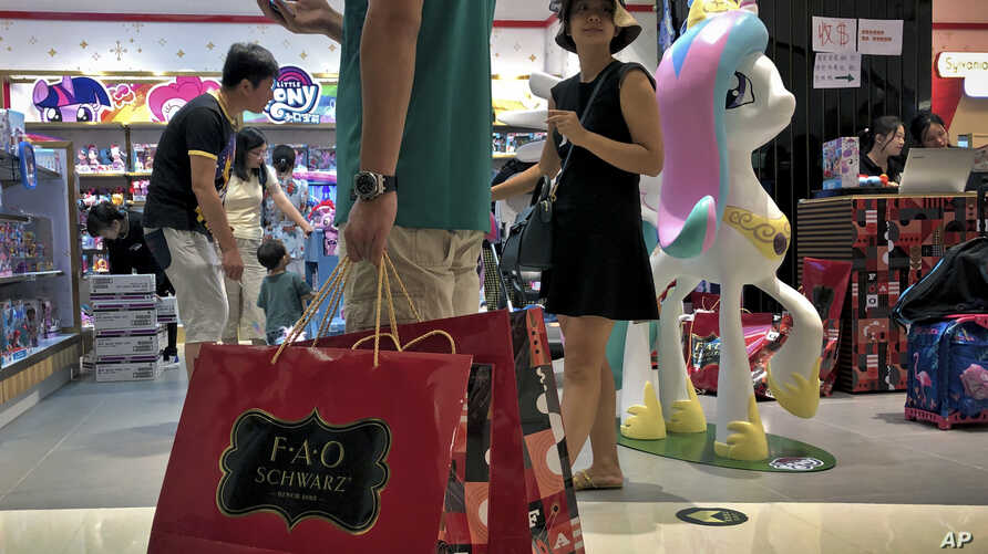 FILE - In this June 1, 2019, photo, file a man carries a paper bags containing toys purchased from the FAO Schwarz as people shop at the newly open FAO Schwarz toy store at the capital city's popular shopping mall in Beijing. Caught in the crossfire…