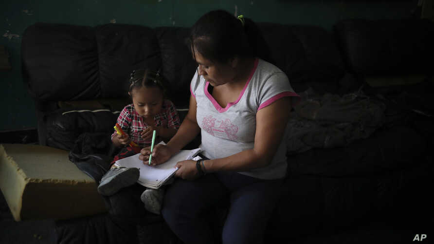 Lucia, 38, from Guerrero state, draws with her youngest daughter as she and her children wait at Agape World Mission shelter for a chance to request asylum in the United States, in Tijuana, Mexico, Friday, Sept. 13, 2019. Lucia fled with her…