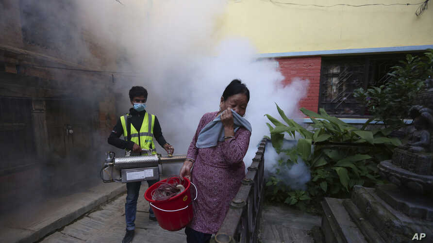 A Nepalese woman covers her face as a worker fumigates an area in an attempt to control the spread of mosquito-borne diseases in Kathmandu, Nepal, Thursday, Sept. 5, 2019. According to the Epidemiology and Disease Control Division under the…