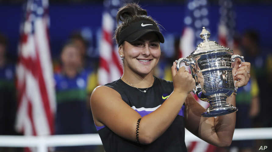 Bianca Andreescu, of Canada, holds up the championship trophy after defeating Serena Williams, of the United States, in the women's singles final of the U.S. Open tennis championships Saturday, Sept. 7, 2019, in New York. (AP Photo/Charles Krupa)