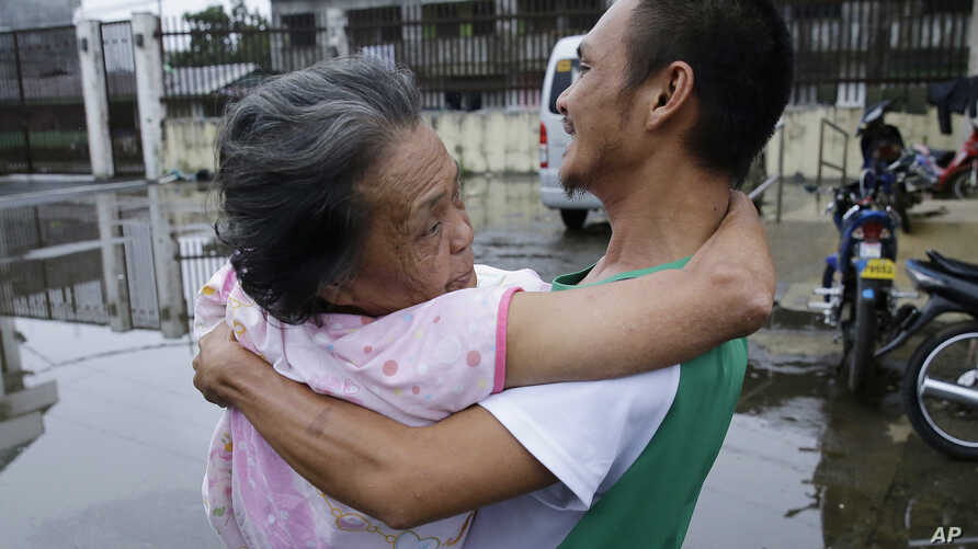 """An elderly woman is carried to a vehicle as they go to an evacuation center in Marawi city, southern Philippines on Thursday, June 8, 2017. Fighting in Marawi between government forces and Muslim militants, led by the so-called """"Maute"""" group, is now…"""