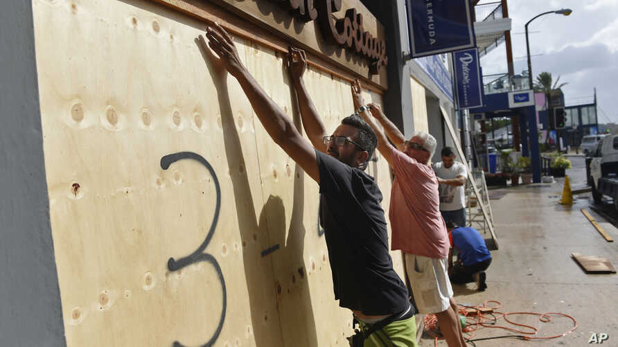 People board up an Urban Cottage store in preparation for Hurricane Humberto in Hamilton, Bermuda, Wednesday, Sept. 18, 2019. Bermuda's government called up troops and urged people on the British Atlantic island to make final preparations for an…