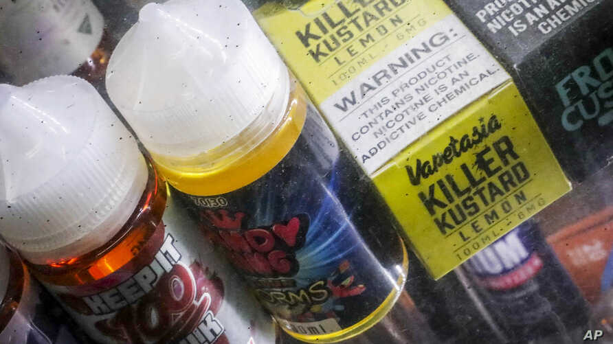 Flavored vaping solutions are shown in a window display at a vape and smoke shop, Monday Sept. 16, 2019, in New York. New York Gov. Andrew Cuomo is pushing to enact a statewide ban on the sale of flavored e-cigarettes amid growing health concerns of…