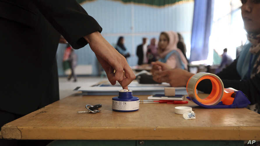 An Afghan woman, left, inks her finger at a polling station at Amani high school, near the presidential palace in Kabul, Afghanistan, Saturday, Sept. 28, 2019. Afghans headed to the polls on Saturday to elect a new president amid high security and…