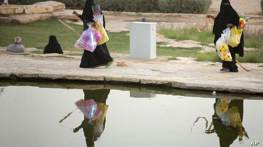 In this March 8, 2018 photo, women sell toys at the garden of the18th century Dir'aiyah fortified complex, that once served as the seat of power for the ruling Al Saud, in Riyadh, Saudi Arabia. (AP Photo/Amr Nabil)