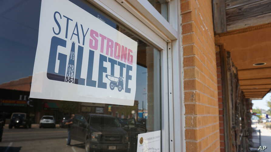 In this Thursday, Sept. 5, 2019 photo shows a poster urging locals to stay strong amid hardship in a Gillette, Wyo, storefront on the Eagle Butte mine just north of Gillette, Wyo. The shutdown of Blackjewel LLC's Belle Ayr and Eagle Butte mines in…