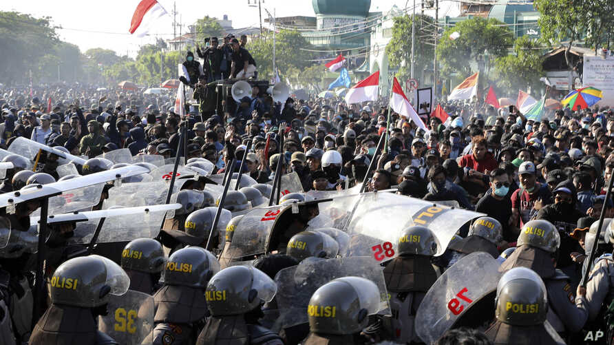Riot police officers block students from advancing towards the local parliament during a rally in Surabaya, East Java, Indonesia, Thursday, Sept. 26, 2019. Protests continue in several cities in the country as students rallied against a new law that…