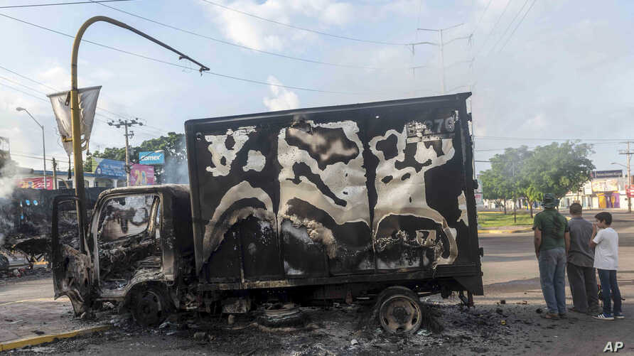 This Oct. 18, 2019 photo shows a burnt out truck used by gunmen smoldering on an intersection, a day after street battles…