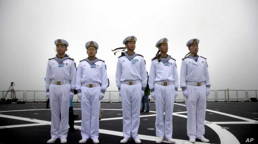 Chinese sailors stand on the deck of the naval training ship Qi Jiguang during a naval parade to commemorate the 70th…