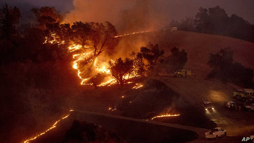 Flames from a backfire, lit by firefighters to slow the spread of the Kincade Fire, burn a hillside in unincorporated Sonoma…