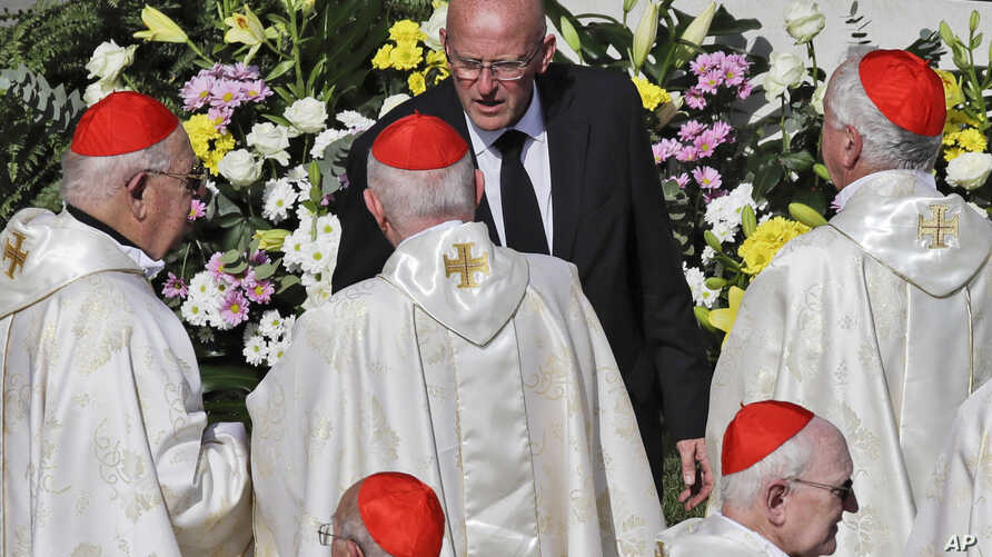 Vatican head of security Domenico Giani, top center, speaks to a group of cardinals during a canonization Mass in St. Peter's…