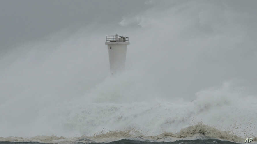 Surging waves hit against the breakwater and a lighthouse as Typhoon Hagibis approaches at a port in town of Kiho, Mie…