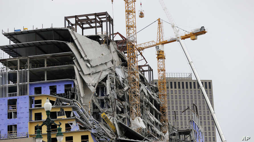 Workers in a bucket hoisted by a crane begin the process of preparing the two unstable cranes for implosion at the collapse…