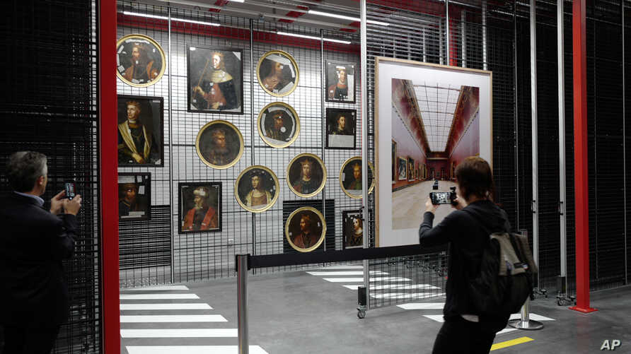 A person takes pictures of paintings at the Louvre Conservation Center, which was inaugurated in Lievin in northern France,…