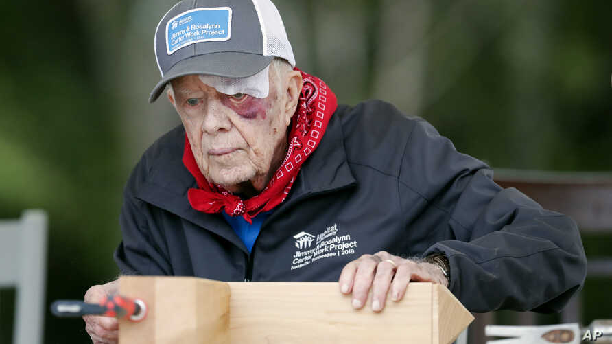 With a bandage above his left eye and a large, red welt below it, former President Jimmy Carter builds corbels at a Habitat for…