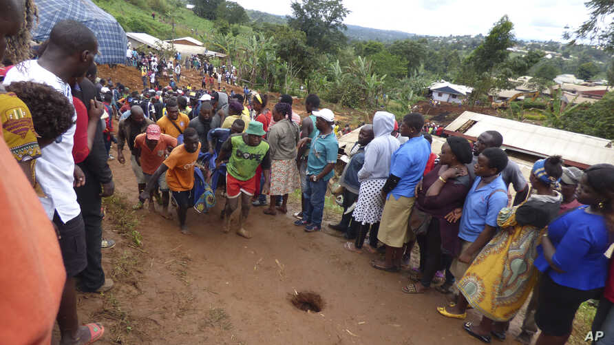Rescue workers carry a body from the rubble of a landslide in Bafoussam, Cameroon