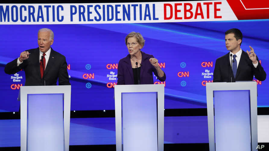 Democratic presidential candidate former Vice President Joe Biden, left, Sen. Elizabeth Warren, D-Mass., center and South Bend…