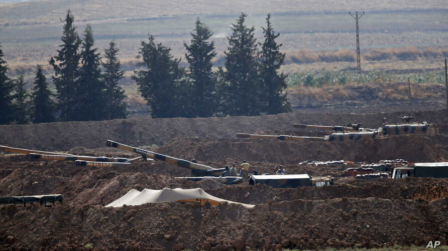 Turkish soldiers are seen on artillery pieces holding their positions near the border with Syria in Sanliurfa province, Turkey,…