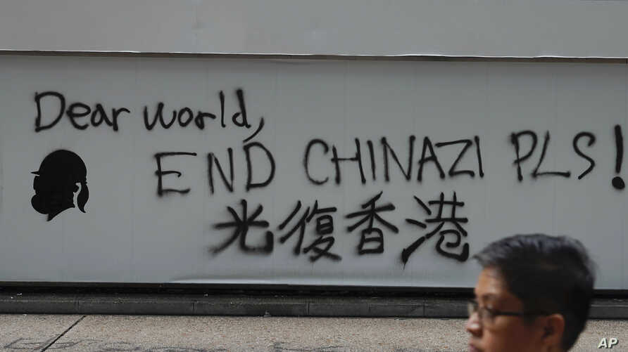 """A man walks past a wall with the words """"Liberate Hong Kong- Dear World End Chinazi Please"""" in Hong Kong, Monday, Oct. 7, 2019…"""