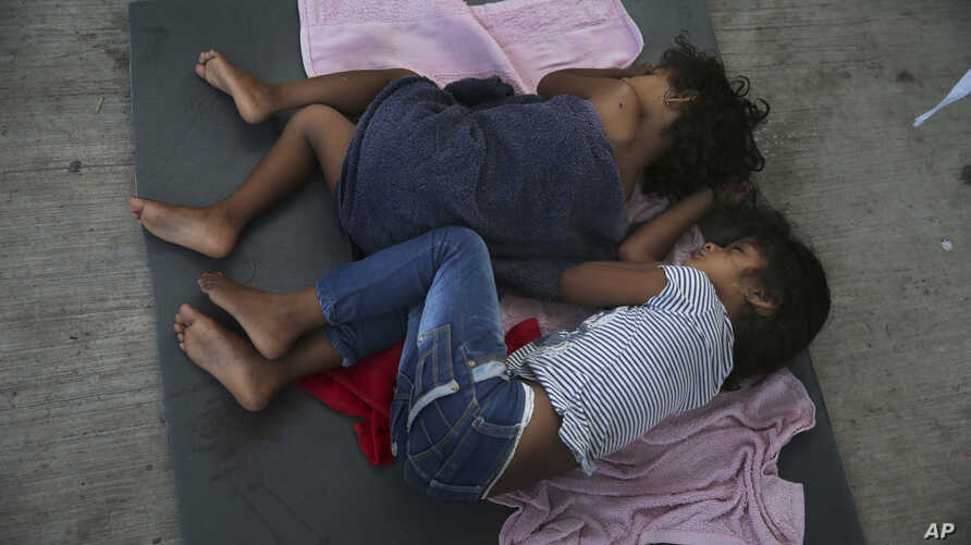 FILE - In this July 17, 2019 file photo, migrant children sleep on a mattress on the floor of the AMAR migrant shelter in Nuevo…