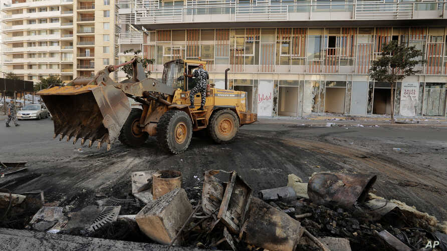 A bulldozer clears the rubble from a street in the aftermath of a protest against the Lebanese government in Beirut, Lebanon,…