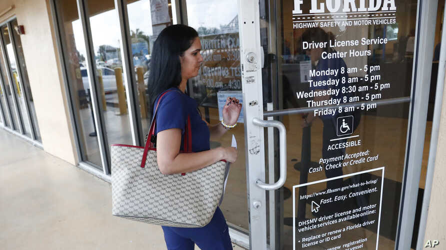 A woman enters a Florida Highway Safety and Motor Vehicles drivers license service center, Tuesday, Oct. 8, 2019, in Hialeah,…