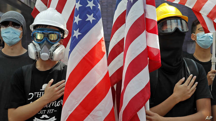 Pro-democracy university students hold U.S. flags and sing the Star-Spangled Banner at the campus of the University of Hong…