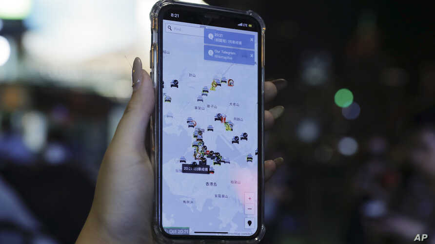 A person's phone shows HKmap.live apps as they join others at a rally to mark Taiwan's National Day, in the Tsim Sha Tsui…