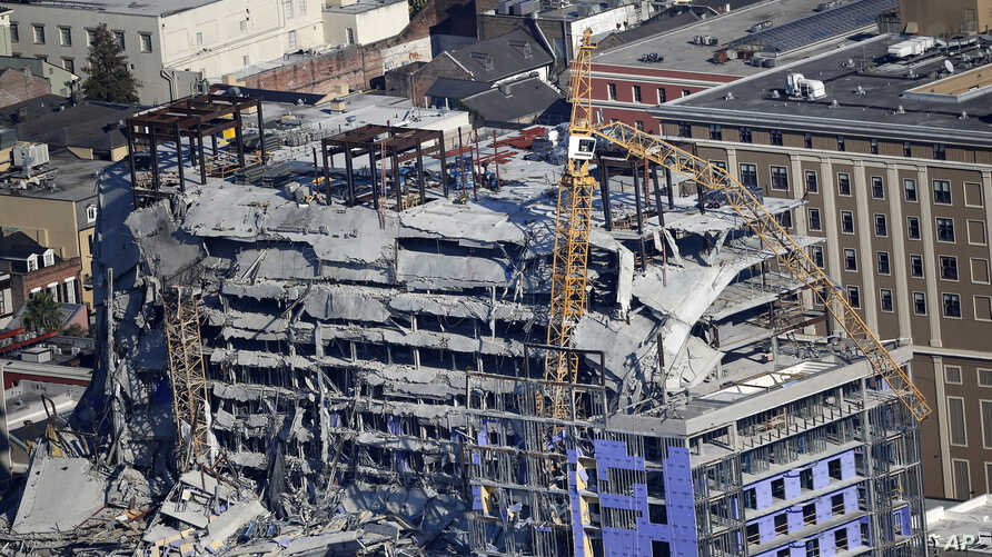 Two large cranes from the Hard Rock Hotel construction collapse are seen in this aerial photo after crashing down, after being…