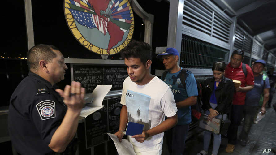 Cuban Abel Oset Jr., center, and his father Abel Oset, behind him, show their identification to a U.S. Customs and Border…