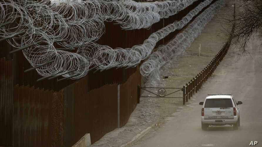 FILE - In this March 2, 2019 file photo a Customs and Border Control agent patrols on the US side of a razor-wire-covered…