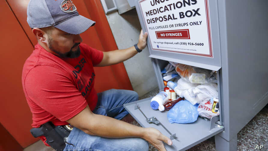 FILE - In this Sept. 11, 2019, photo, narcotics detective Paul Laurella retrieves unused medications from the police department…