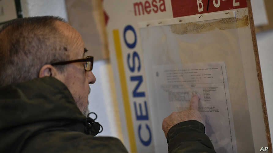 A man checks a panel at a polling station before casting his vote for the general election in Pamplona, northern Spain, Sunday,…