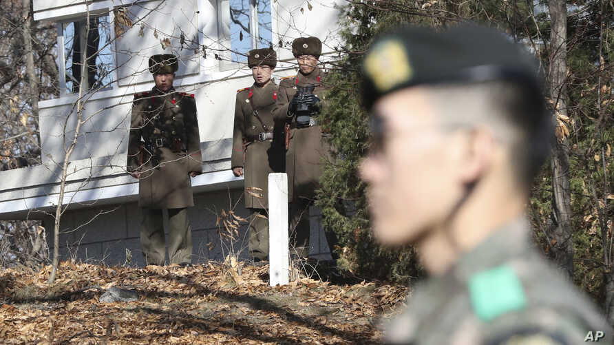 FILE - In this Nov. 27, 2017, file photo, North Korean soldiers look at the South side as a South Korean stands guard near the…