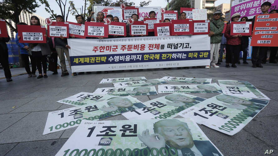 Fake bank notes showing images of U.S. President Donald Trump are displayed as protesters stage a rally to oppose the United…