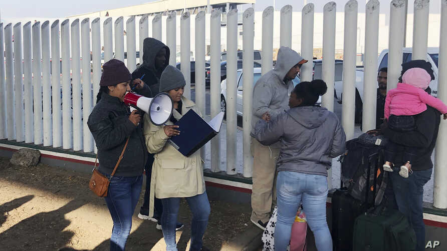 In this Nov. 12, 2019, photo, volunteers call names of people on a waiting list trying to obtain asylum in the United States…
