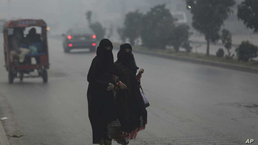 People cross a road engulfs in smog in Lahore, Pakistan, Friday, Nov. 22, 2019. Tens of thousands of people in Pakistan's…