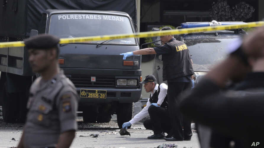 Members of police forensic team inspect the site of a bombing attack at the local police headquarters in Medan, North Sumatra,…