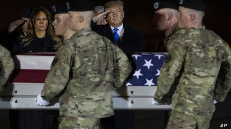 President Donald Trump and first lady Melania Trump look on as a U.S. Army carry team moves a transfer case containing the…