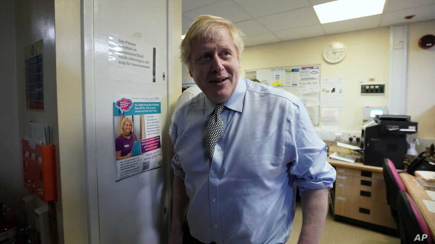 Prime Minister Boris Johnson looks on as he visits Bassetlaw District General Hospital, during their General Election campaign…