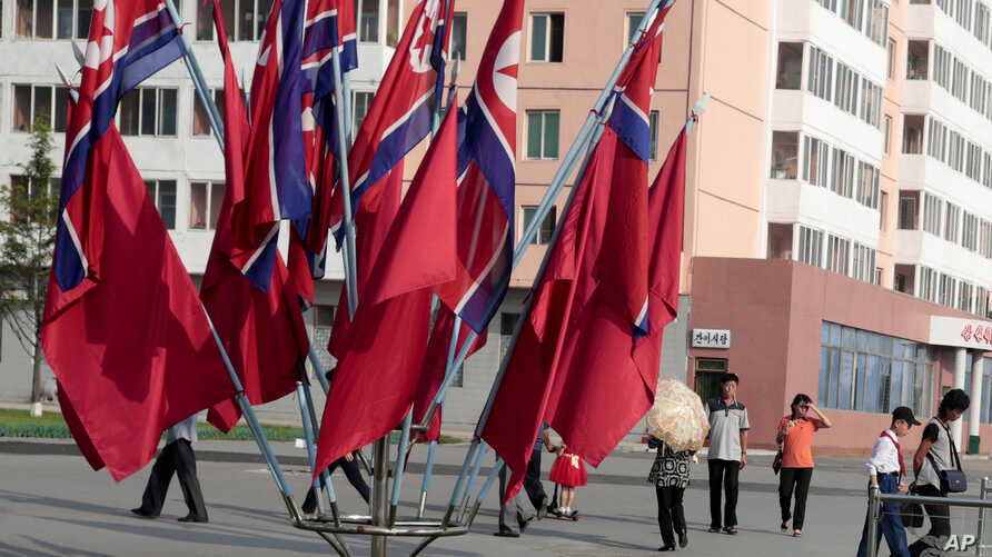 Locals walk past North Korean national flags displayed during the celebration of the 71st anniversary of the founding of the…