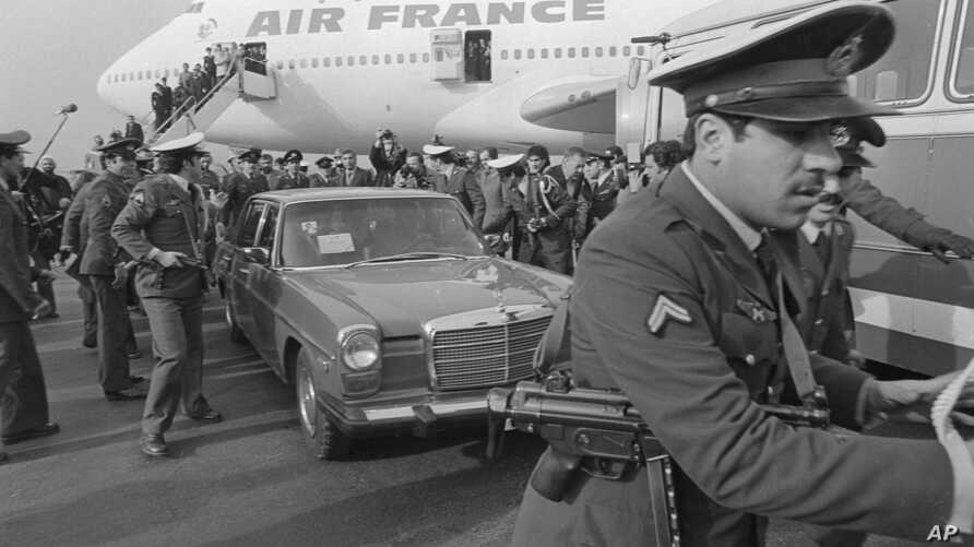 FILE - In this Feb. 1, 1979 file photo, Ayatollah Ruhollah Khomeini has a heavy escort as he enters car to leave the airport in…