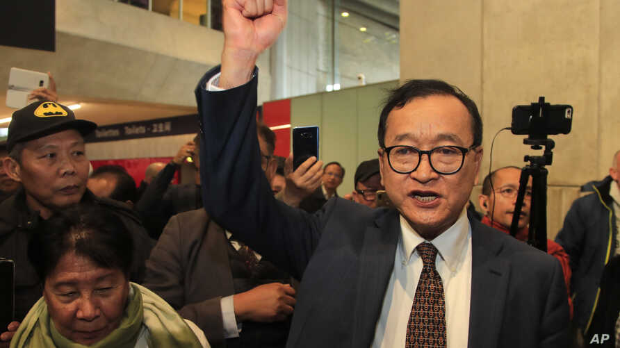 Cambodia's most prominent opposition politician Sam Rainsy clenches his fist as he is attempting to return to Cambodia Thursday…
