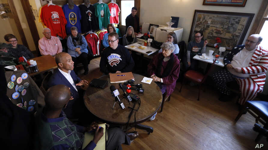 Democratic presidential candidate former Massachusetts Gov. Deval Patrick, left, speaks to local residents during a stop at the…