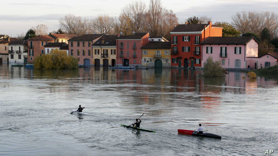 Canoeists sail their way as water reaches the houses after the Ticino river overflowed its banks, in Pavia, Italy, Monday, Nov…