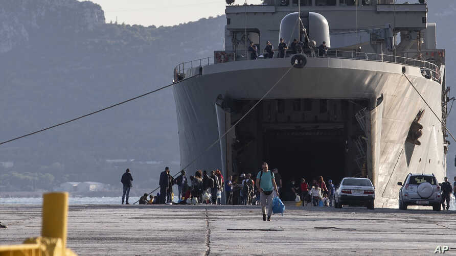 Migrants wait outside a military vessel after their disembarkation at the port of Elefsina, near Athens, on Saturday, Nov. 2,…