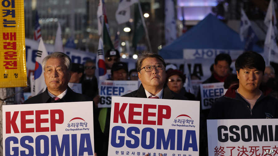 South Koreans hold banners during a rally to demand to keep the General Security of Military Intelligence Agreement, or GSOMIA,…