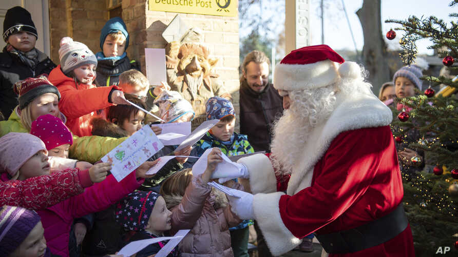 A man dressed as Santa Claus is welcomed by children during the opening of the most famous German Christmas mail office in the…