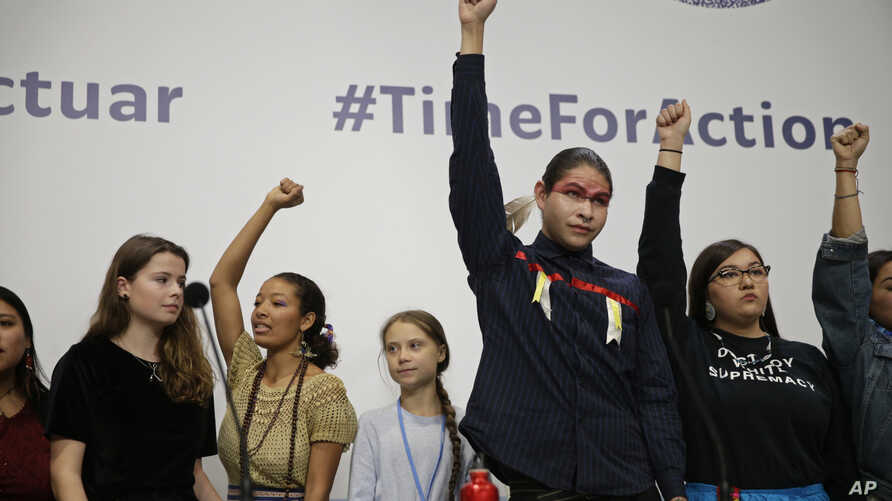 Climate activist Greta Thunberg, centre, stands with other young activists at the COP25 Climate summit in Madrid, Spain, Monday…