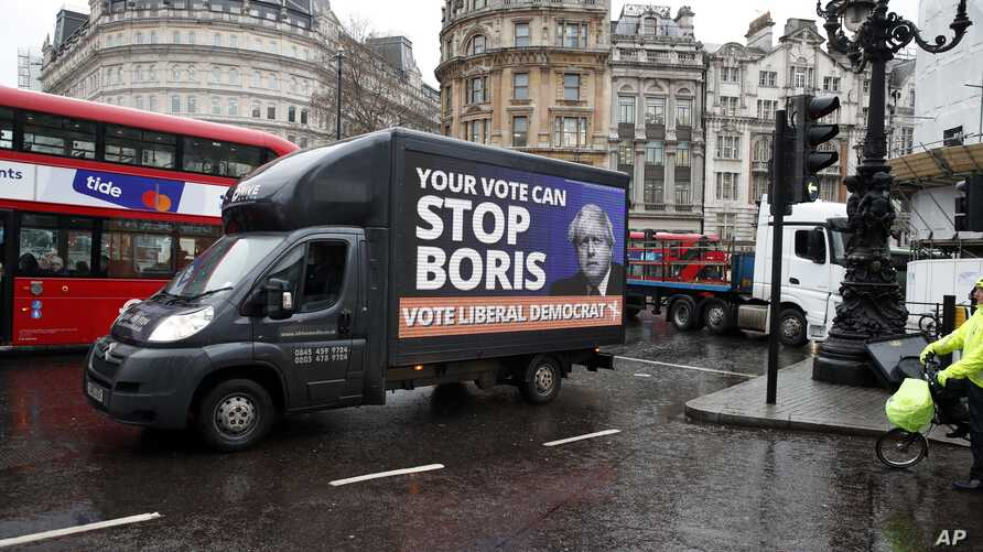 A vehicle brandishing an election campaign poster for the Liberal Democrats party, drives in Trafalgar Square in London,…